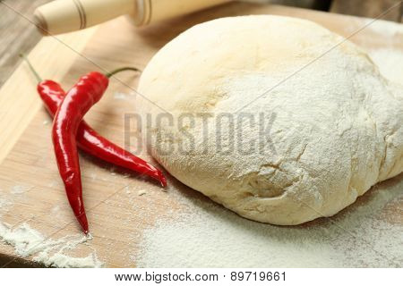 Dough on cutting board with chili close up