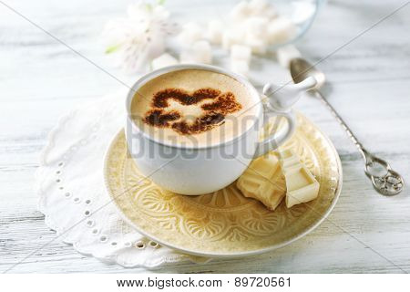 Cup of latte coffee art on wooden table, on light background