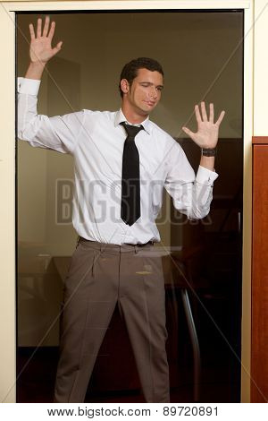 Businessman making face on glass wall