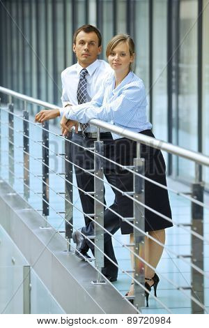 Portrait of businessman and businesswoman standing by railing