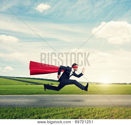 serious businessman wearing like superhero very fast running on the road over green fields and blue sky