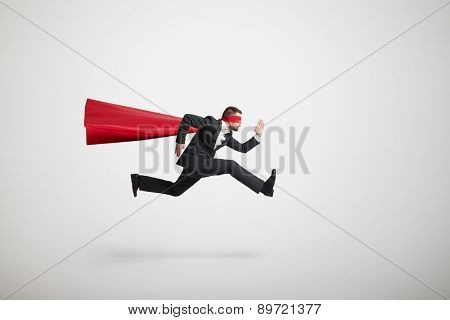 serious businessman wearing like superhero very fast running over light grey background