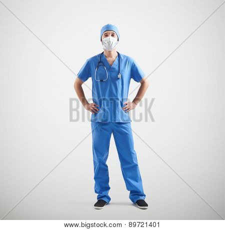 full-length portrait of nurse in blue uniform and mask over light grey background