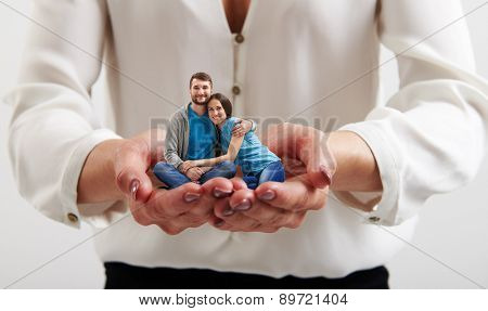 big womans hands holding small happy couple in love