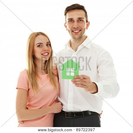 Attractive young couple with decorative house, isolated on white