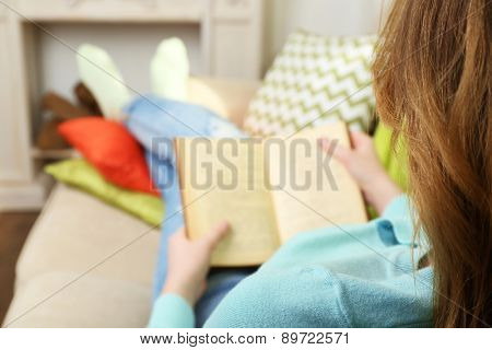 Woman reading book on sofa in room