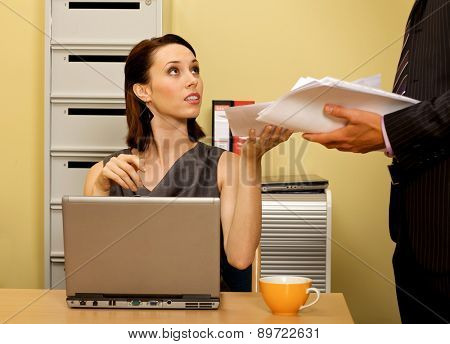 Young businesswoman receiving documents from businessman
