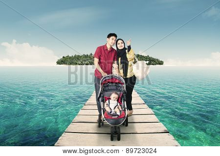 Parents With Their Baby In The Stroller At Pier