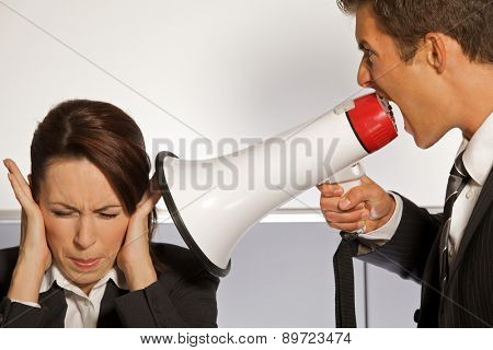 Businesswoman shouting at businessman through megaphone