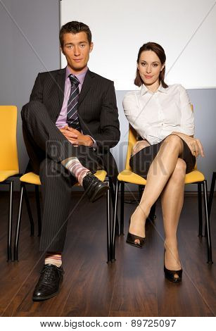 Portrait of businessman and businesswoman sitting in waiting room