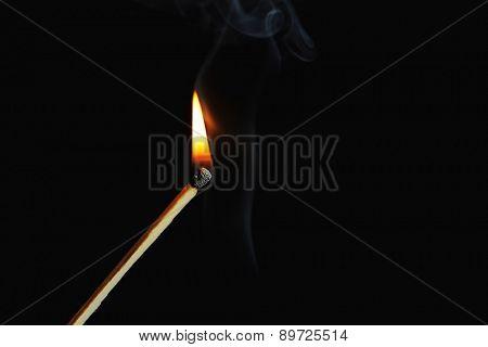 Burning match with smoke on dark background