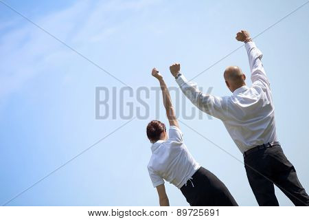 Rear view of business couple with arms outstretched standing in park