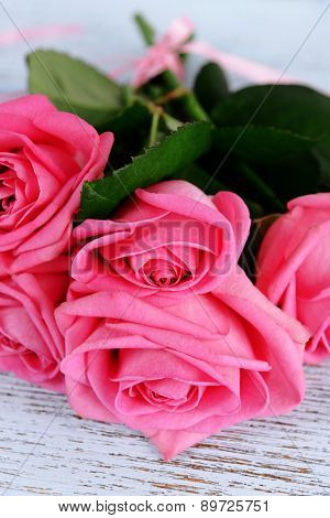 Beautiful pink roses on wooden table, closeup