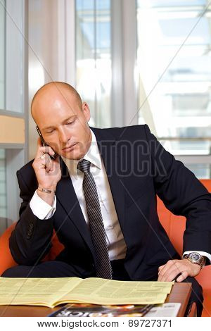 Businessman conversing on mobile phone while reading newspaper