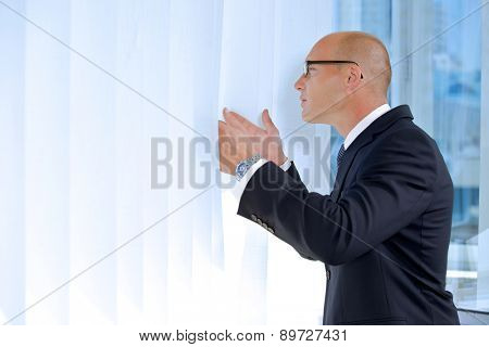 View of businessman looking through window