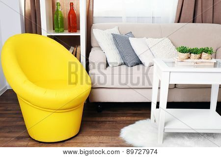 Modern interior with comfortable sofa and chair in room