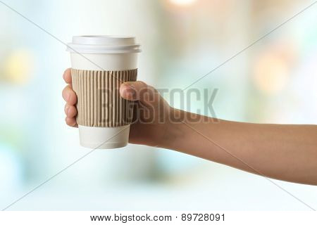 Hand holding paper cup of coffee on bright background