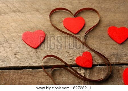 Magnetic tape in shape of heart on wooden background