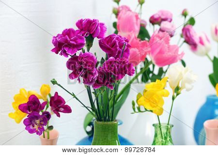 Different beautiful flowers in vases close up