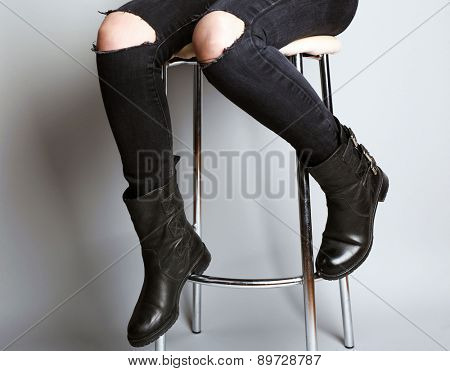 Girlish legs in torn jeans on gray background