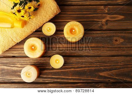 Soft towel with candles on table close up