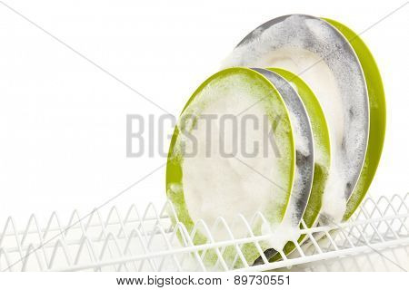 Plates with foam in rack isolated on white