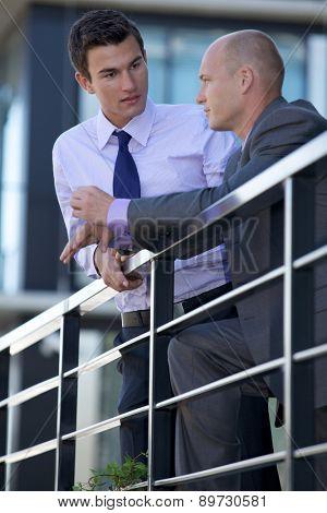 Businessmen in conversation by railing