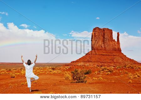 Navajo Reservation in the US. Red Desert and freestanding sandstone cliffs. Woman in white doing yoga under a long rainbow