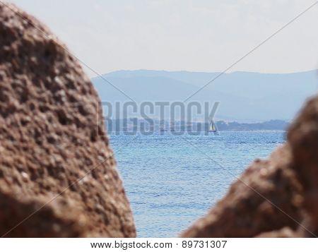 Seascape Of Tavolara Island On Blurred Rocks Foreground