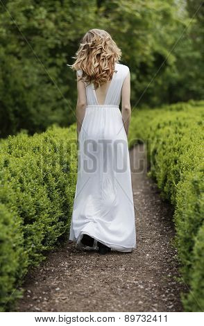 Young girl walking on an alley in the park