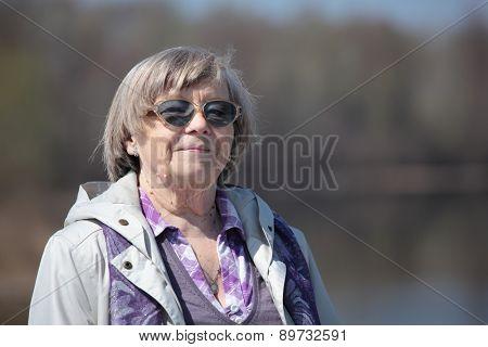 Senior woman against a river in springtime