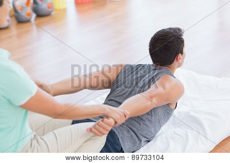 Man stretching with his trainer in fitness studio