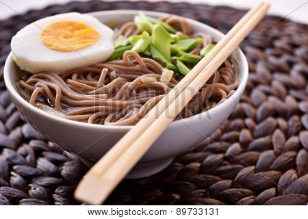Soba noodle soup with boiled egg and green onion. Selective focus on the noodles