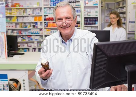 Pharmacist holding medicines looking at camera at pharmacy