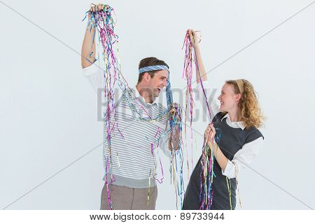Happy geeky couple dancing on white background