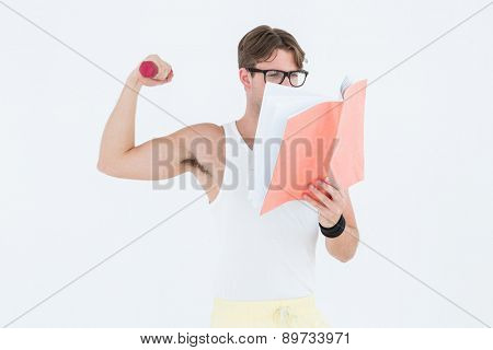 Geeky hipster lifting dumbbells and reading notepad on white background