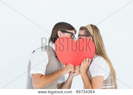 Geeky hipsters kissing behind heart card on white background