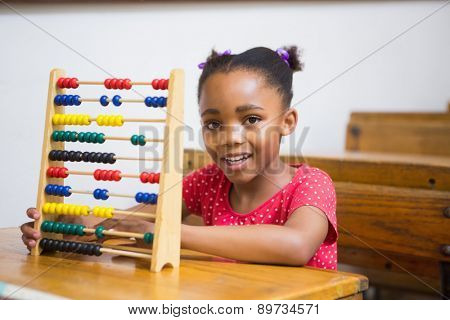 Smiling pupil using abacus in classroom at elementary school