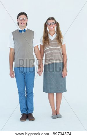 Geeky hipster couple holding hands on white background