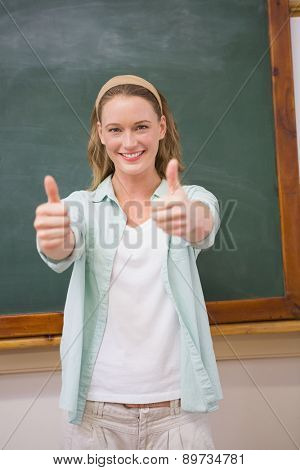 Teacher smiling at camera with thumbs up at elementary school