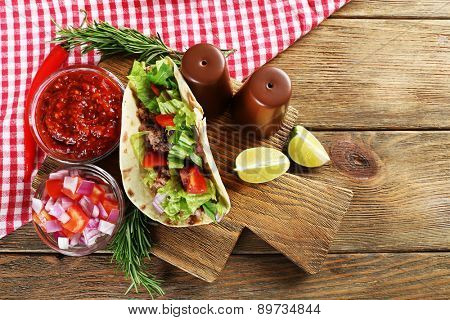 Mexican food Taco on wooden cutting board, closeup