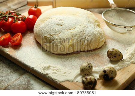 Dough on cutting board with cherry and quail eggs on table close up