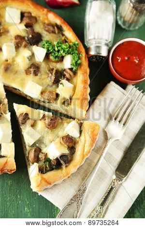Cheese pie with mushrooms, herbs and sour creme, on napkin, on color wooden table background