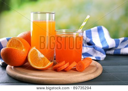 Glass of healthy fresh juice of apples and carrots on wooden background