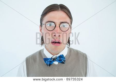 Geeky hipster looking surprised at camera on white background