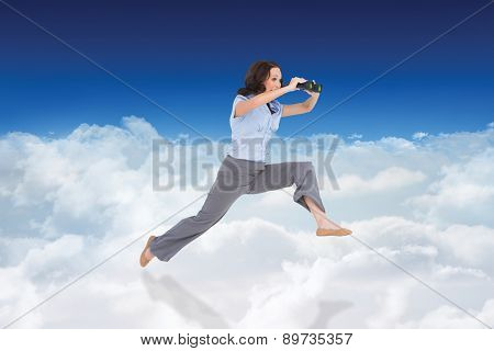 Cheerful classy businesswoman jumping while holding binoculars against bright blue sky over clouds