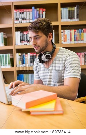 Student studying in the library with laptop at the university