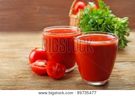 Glasses of fresh tomato juice on wooden background