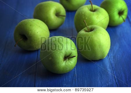 Green apples on color wooden background