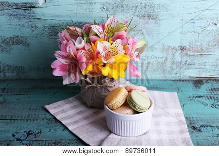 Delicious macaroon with beautiful flowers on wooden background